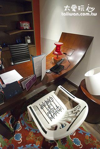 彎曲的桌子搭配塑膠椅,以及圖釘桌燈反映出超現實主義風格