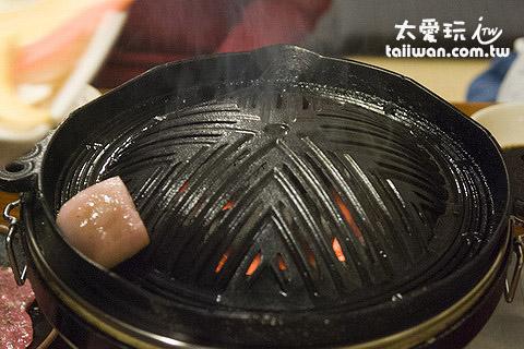 服務生先拿一塊油在鐵盤上塗抹出油