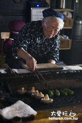 廚師坐在炭烤爐前為大家料理